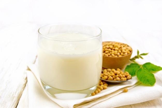 Sojamelk in een glas, groen blad, sojabonen in een lepel en kom op een servet tegen de achtergrond van een licht houten bord