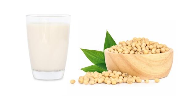 Sojamelk met sojabonen die op witte achtergrond worden geïsoleerd.