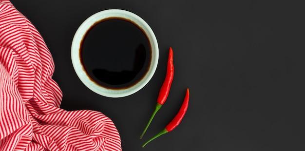 Sojasaus in kom en rode spaanse peperpeper op zwarte achtergrond met het horizontale bannerformaat van de exemplaarruimte. aziatisch eten concept, bovenaanzicht