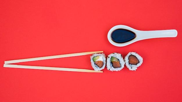 Sojasaus in lepel met eetstokjes en sushi op rode achtergrond