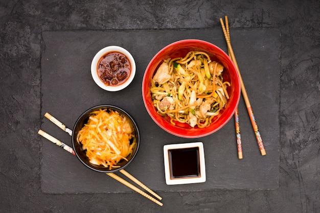 Sojasaussalade en eetstokje met smakelijke kippennoedels op zwarte oppervlakte