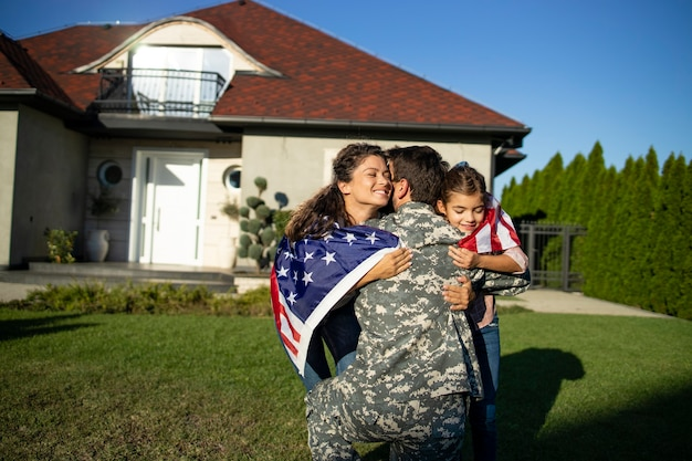 Soldaat die naar huis komt en zijn familie met amerikaanse vlag die in zijn armen loopt om reünie te vieren