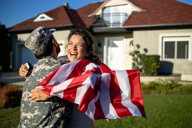 Soldaat die thuiskomt en zijn vrouw met amerikaanse vlag die in zijn armen rent om de reünie te vieren