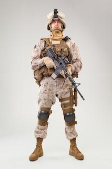 Soldaat in amerikaanse mariniersuniform met geweer op lichtgrijze muur,