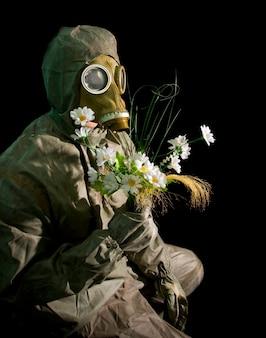 Soldaat in beschermende kleding en gasmasker met bloemen op zwart