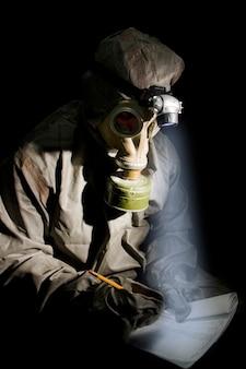Soldaat in beschermende kleding en gasmasker met notitieblok en potlood op briefing.