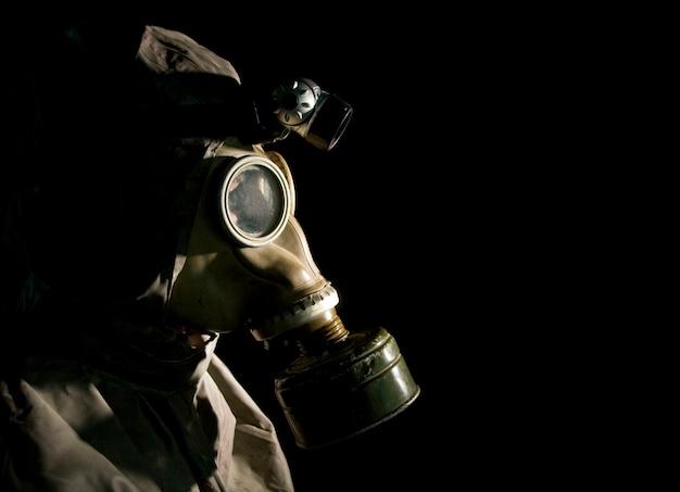 Soldaat in beschermende kleding en gasmasker op zwart