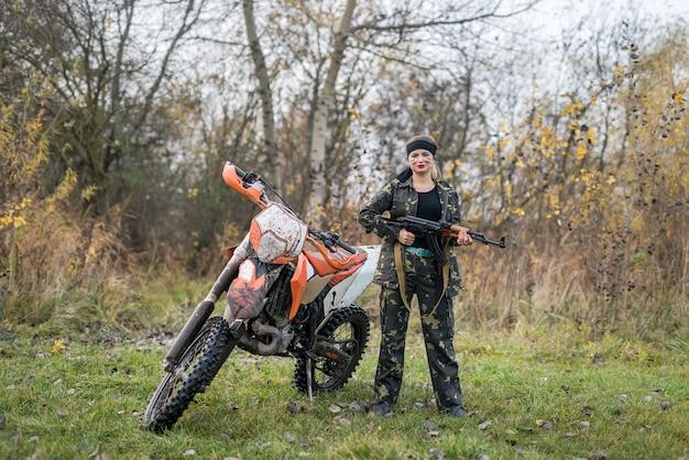 Soldaat in camouflage met geweer en vuile motorfiets