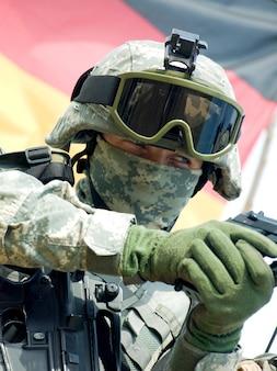 Soldaat in camouflage-uniform die zijn geweer richt