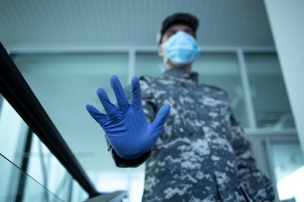 Soldaat in camouflage uniform dragen van beschermende handschoenen en masker met stopbord bij de ingang van het ziekenhuis