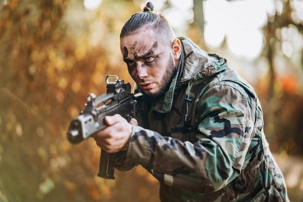 Soldaat in camouflage uniform en geschilderd gezicht is gericht.