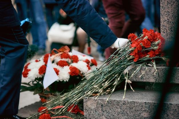Soldaat in witte handschoenen zet bloemen op het monument voor soldaten die stierven in de tweede wereldoorlog