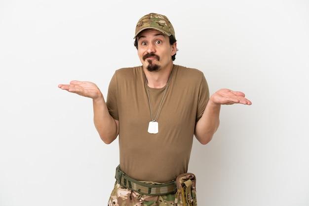 Soldaat man geïsoleerd op een witte achtergrond die twijfels heeft terwijl hij zijn handen opsteekt