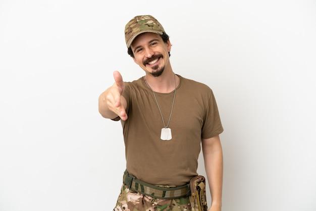 Soldaat man geïsoleerd op een witte achtergrond handen schudden voor het sluiten van een goede deal