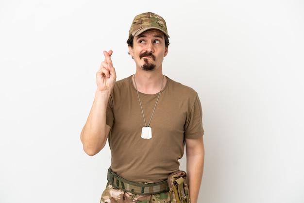 Soldaat man geïsoleerd op een witte achtergrond met vingers die kruisen en het beste wensen