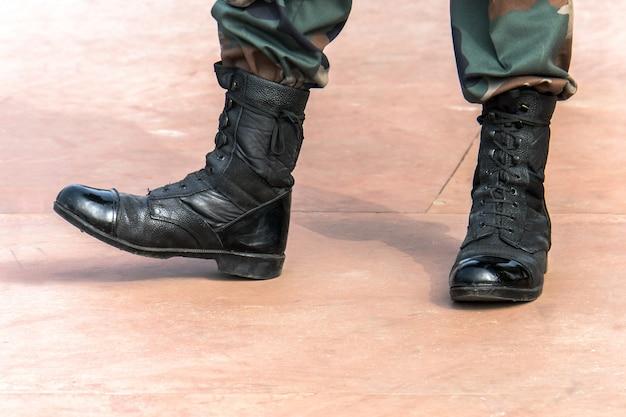 Soldaat op de top van een berg legerlaarzen. zwart gelakte soldatenlaarzen. soldaten op de mars.