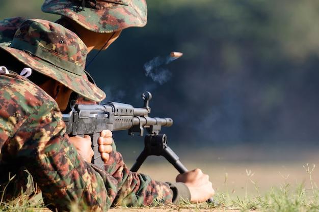 Soldaat schiet geweergeweer naar doelwit met kogelpatroon in de lucht