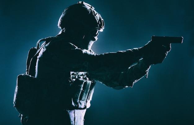 Soldaat van de elitetroepen van het leger, speciale veiligheidsdienstjager met verborgen achter masker en brilgezicht, in helm en lastwagensysteem, gericht met servicepistool low key, zijaanzicht, studio-opname