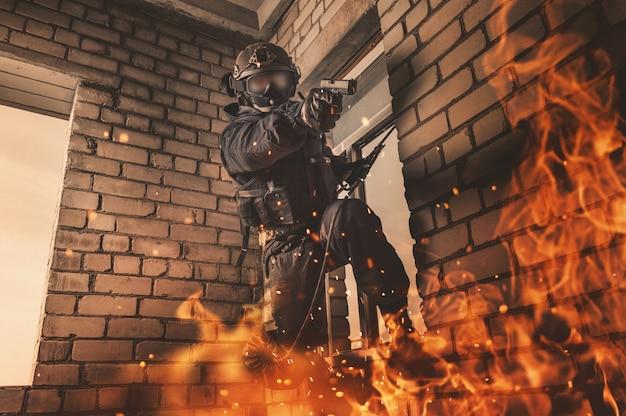 Soldaat van de special forces bevrijdt gijzelaars uit een gebouw dat in brand staat. swat