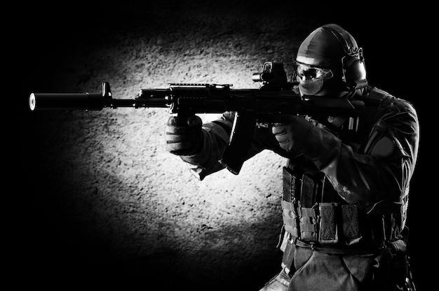 Soldaat van een speciale eenheid staat met een pistool in zijn handen en richt zich op het doelwit. gemengde media