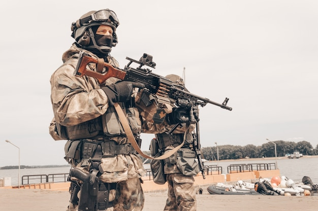 Soldaat van een speciale troepengroep staat met een zwaar machinegeweer. speciaal operaties concept.