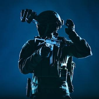 Soldaat voor speciale operaties, swat-teamjager met masker en bril, uitgerust nachtzichtapparaat, bewapend dienstgeweer met korte loop, terugkijkend en bevriezend handsignaal tonend, rustige studio-opname