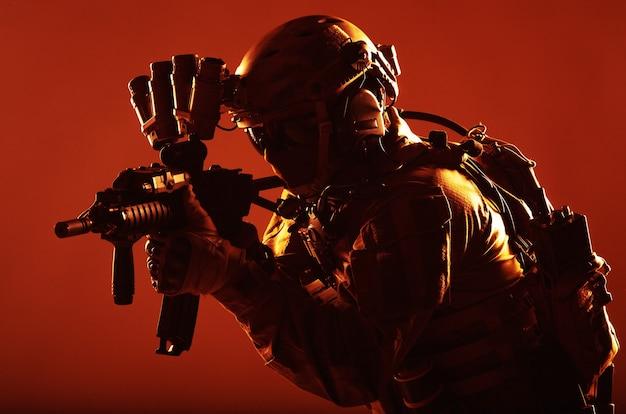 Soldaat voor speciale operaties van het leger, commandojager in volledige tactische munitie, helm met radioheadset en nachtzichtapparaat, gericht op een aanvalsgeweer met korte loop in het donker, rustige studio-opname