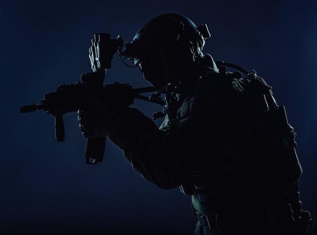 Soldaat voor speciale operaties van het leger, lid van het team voor terrorismebestrijding van de politie, schutter van de veiligheidsdienst met masker, helm met headset en nachtzichtapparaat, gewapend dienstgeweer met korte loop