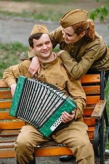 Soldaat zit op een bankje, speelt een accordeon en vrouwelijke soldaat achter