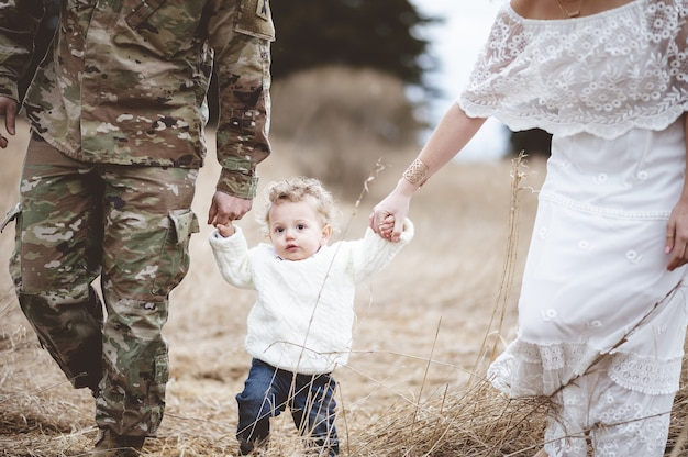 Soldaatvader met zijn vrouw die de handen van hun zoon van beide kanten vasthoudt en in een veld loopt