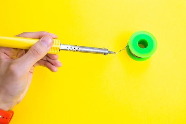 Soldeerbout, tin, hars op een gele tafel. soldeerbout in mannelijke handen. reparatie van elektrische apparatuur, radiotechniek. soldeerdraden, contacten.