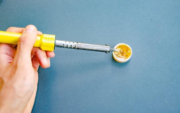 Soldeerbout, tin, hars op een zwarte tafel. soldeerbout in mannelijke handen. reparatie van elektrische apparatuur, radiotechniek. soldeerdraden, contacten.