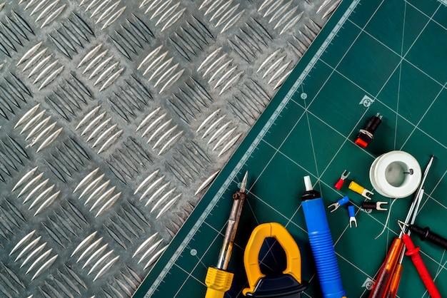 Soldeergereedschap. soldeerbout, spoel soldeerdraad, schroevendraaier, soldeerloze geïsoleerde spadeklemmen op industriële metalen schijf en groene snijmat.