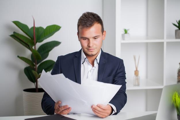 Solide zakenman in een jas werkt met documenten in het kantoor van het bedrijf