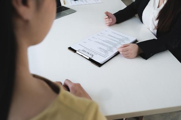 Sollicitatiegesprek in kantoorconcept, focus op cv-papier, werkgever beoordeelt goed cv van voorbereide bekwame sollicitant, recruiter overweegt sollicitatie of hr-manager die een wervingsbeslissing neemt