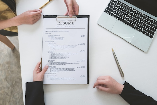 Sollicitatiegesprek in kantoorconcept, focus op cv-papier, werkgever beoordeelt goed cv van voorbereide bekwame sollicitant, recruiter overweegt sollicitatie