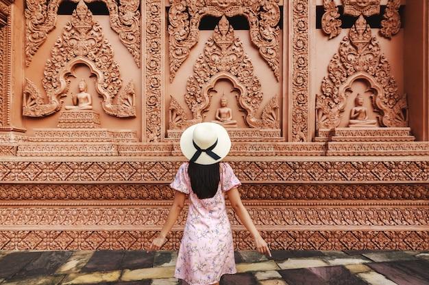 Solo reizen ontspannen vakantie concept, jonge gelukkig aziatische reiziger vrouw met hoed sightseeing in wat tham phu wa tempel, kanchanaburi, thailand