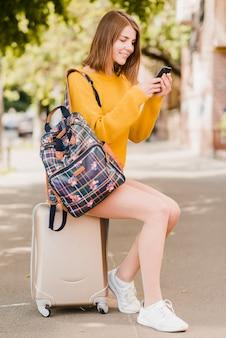 Solo reizende vrouw die haar telefoon controleert