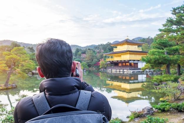 Solo-toerist die foto's maakt met de camera in de kinkakuji-tempel of het gouden paviljoen in het herfstseizoen, aziatische reizigersbezoek in kyoto, japan. vakantie, bestemming en reisconcept