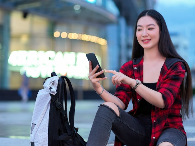 Solo vrouwelijke backpacker die mobiele telefoon gebruikt om online taxiservice te boeken en hotel te boeken