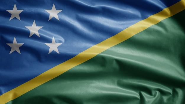 Solomon islander vlag zwaaien in de wind. close-up salomon islander banner waait, zachte en gladde zijde. doek stof textuur vlag achtergrond. gebruik het voor het concept van nationale dag en landgelegenheden.