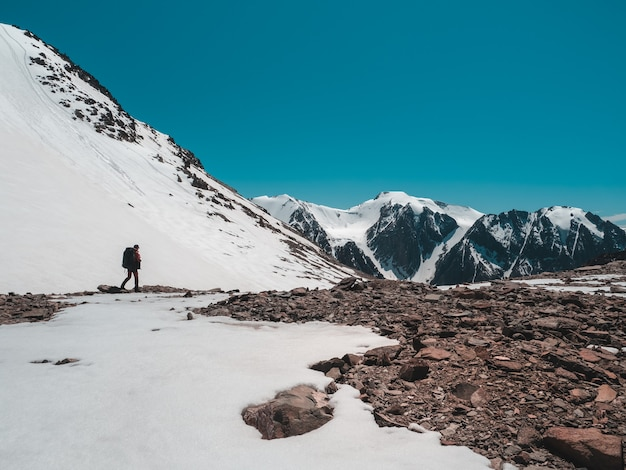 Solowandeling langs de met sneeuw bedekte bergen. extreme recreatie en bergtoerisme. een mannelijke wandelaars langs het bergpad. op de achtergrond grote besneeuwde bergen. ruimte kopiëren.