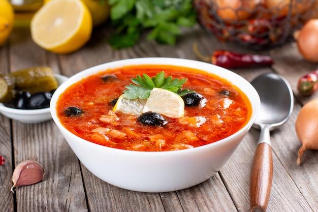 Solyanka, russische soep met worst, olijven, ingelegde komkommer en kappertjes
