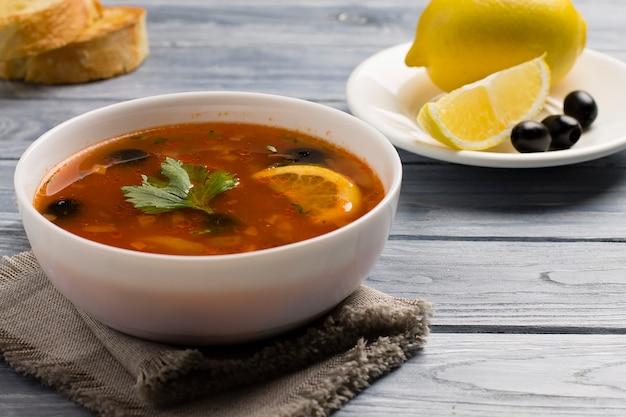 Solyanka-soep met vlees, worst, groenten, olijven en citroen in een bord.
