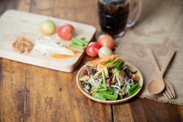 Som tam thai, thai papaya salad op houten achtergrond