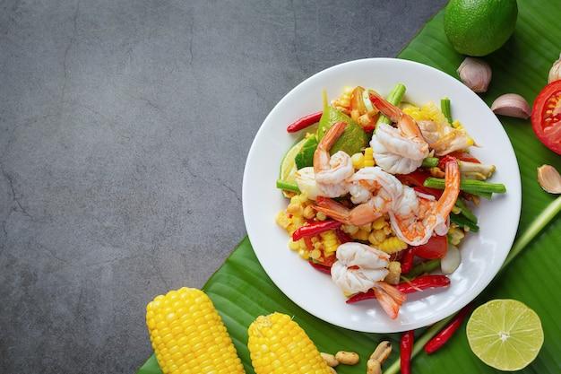 Som tum met maïs en garnalen, geserveerd met rijstnoedels en groene salade versierd met thaise voedselingrediënten.