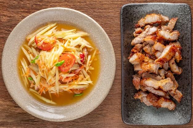 Som tum thai, som tam thai, thais eten, pittige papaya salade en gebakken varkensvlees in keramische plaat op rustieke natuurlijke houtstructuur achtergrond, bovenaanzicht