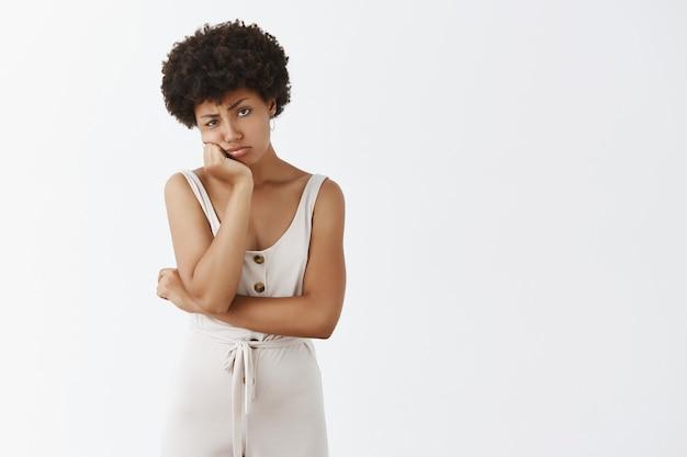 Somber en droevig stijlvol meisje poseren tegen de witte muur