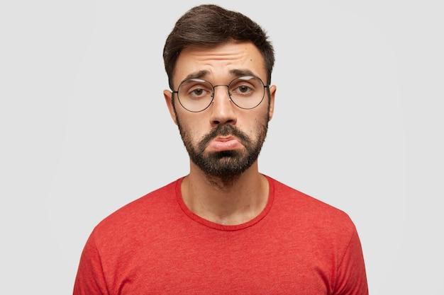 Somber ontevreden bedroefd bebaarde jonge man tuitt lippen van ontevredenheid, beledigd door slechte opmerkingen van volgers, drukt negativiteit uit, draagt een rood jasje, staat tegen een witte muur