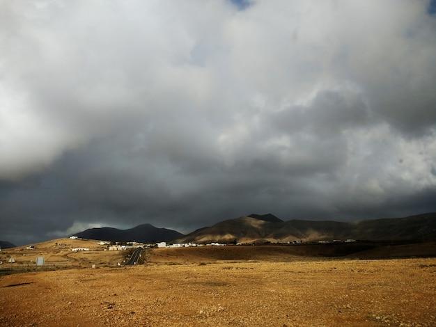 Sombere bewolkte hemel en een zanderig land van fuerteventura, spanje.